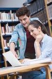 Camarades de classe étudiant ensemble à la bibliothèque Images stock