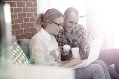 Camarades de classe buvant du café et travaillant sur un ordinateur Images libres de droits