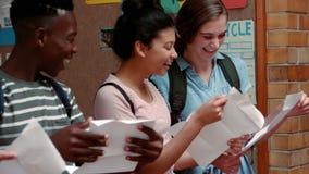 Camarades de classe heureux regardant des cartes de catégorie dans le couloir clips vidéos