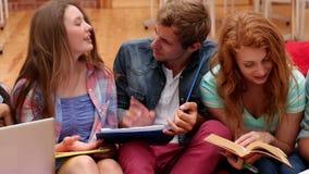 Camarades de classe heureux s'asseyant sur des fauteuils poire dans la chambre commune clips vidéos