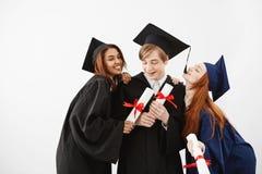 Camarades de classe licenciés gais célébrant la réjouissance de sourire au-dessus du fond blanc Photos stock