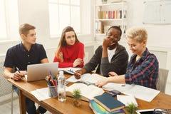 Camarades de classe multi-ethniques se préparant aux examens ensemble Image stock