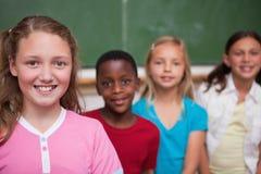 Camarades de classe posant dans une ligne Image libre de droits