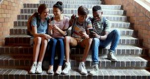 Camarades de classe s'asseyant sur l'escalier et à l'aide du téléphone portable banque de vidéos