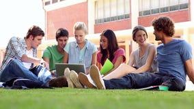 Camarades de classe s'asseyant sur la causerie d'herbe clips vidéos