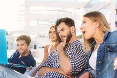 Camarades observant un film ensemble sur la plage Photo libre de droits