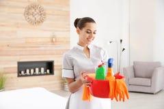 Camareira nova com fontes de limpeza na sala de hotel imagem de stock royalty free