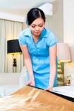 Camareira que faz a cama na sala de hotel asiática fotografia de stock