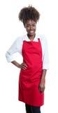 Camarera afroamericana hermosa con el pelo rizado y el delantal rojo foto de archivo libre de regalías