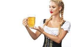 Camarera atractiva joven de Oktoberfest, llevando un vestido bávaro tradicional, taza de cerveza de servicio en el fondo blanco Foto de archivo libre de regalías