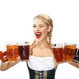 Camarera atractiva joven de Oktoberfest, llevando un vestido bávaro tradicional, tazas de cerveza grandes de servicio en blanco Fotos de archivo libres de regalías