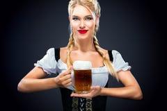 Camarera atractiva joven de Oktoberfest, llevando un vestido bávaro tradicional, tazas de cerveza grandes de servicio en fondo tr Imágenes de archivo libres de regalías