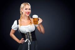 Camarera atractiva joven de Oktoberfest, llevando un vestido bávaro tradicional, tazas de cerveza grandes de servicio en fondo ne Fotos de archivo
