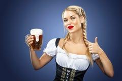 Camarera atractiva joven de Oktoberfest, llevando un vestido bávaro tradicional, tazas de cerveza grandes de servicio en fondo az Imagen de archivo libre de regalías