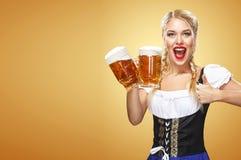 Camarera atractiva joven de Oktoberfest, llevando un vestido bávaro tradicional, tazas de cerveza grandes de servicio en fondo az Imagenes de archivo