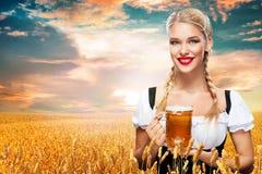 Camarera atractiva joven de Oktoberfest, llevando un vestido bávaro tradicional, tazas de cerveza grandes de servicio en fondo az Fotos de archivo libres de regalías