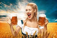 Camarera atractiva joven de Oktoberfest, llevando un vestido bávaro tradicional, tazas de cerveza grandes de servicio en fondo az Fotografía de archivo libre de regalías