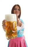 Camarera bávara que sostiene una taza de cerveza de Oktoberfest Imagen de archivo libre de regalías
