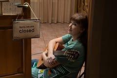 Camarera con una guitarra que se sienta en el piso en el café Fotografía de archivo