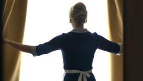 Camarera de las cortinas de abertura del hotel de lujo en el mejor traje, yendo al sitio limpio almacen de video