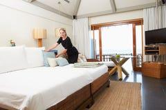 Camarera del hotel que hace la cama de la huésped imagenes de archivo