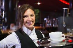 Camarera feliz que sostiene la bandeja con café Imagen de archivo