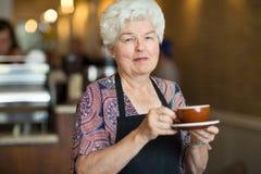 Camarera Holding Coffee Cup y platillo en café Foto de archivo