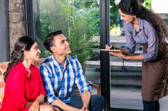 Camarera india que toma órdenes en café o restaurante fotos de archivo libres de regalías