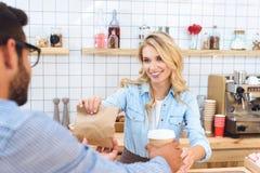 camarera joven sonriente que da el café para ir y la bolsa de papel con la comida al cliente foto de archivo