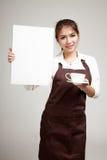 Camarera o barista en el delantal que lleva a cabo el café y la muestra en blanco fotos de archivo