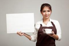 Camarera o barista en el delantal que lleva a cabo el café y la muestra en blanco imágenes de archivo libres de regalías