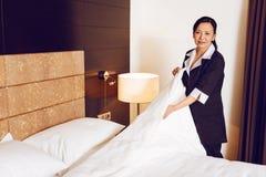 Camarera positiva que pone el edredón sobre las almohadas Imagen de archivo libre de regalías