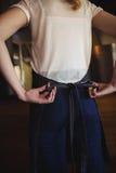 Camarera que ata el delantal en el restaurante Fotos de archivo