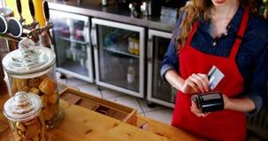 Camarera que birla la tarjeta de crédito en el contador metrajes