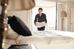 Camarera que coloca el lino en la cama de la habitación, opinión de ángulo bajo imagenes de archivo