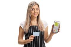 Camarera que lleva a cabo una tarjeta de crédito y un terminal del pago fotos de archivo