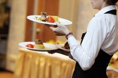 Camarera que lleva tres placas con el plato de la carne Imagen de archivo