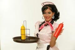 Camarera que muestra una botella de salsa de tomate imagenes de archivo