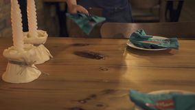 Camarera que pone los cubiertos en la tabla servida para igualar la cena con la vela en restaurante de lujo Porción de la camarer metrajes