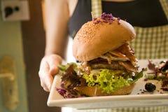 Camarera que sirve la hamburguesa grande Foto de archivo