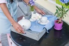 Camarera que sostiene la bandeja con la tabla del juego de té y del servicio en café al aire libre Foto de archivo libre de regalías