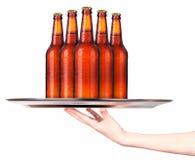 Camarera que sostiene la bandeja con las botellas de cerveza aislada foto de archivo