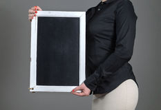 Camarera que sostiene la pizarra verticalmente Fotos de archivo libres de regalías