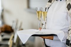 Camarera que sostiene un plato del champán y de las copas de vino en un poco de FE fotos de archivo