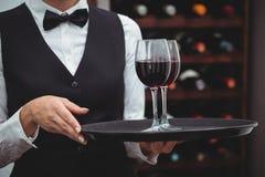 Camarera que sostiene una bandeja con los vidrios de vino rojo Imagenes de archivo