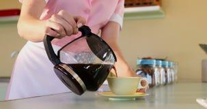 Camarera que vierte el café sólo en taza en el restaurante 4k almacen de video