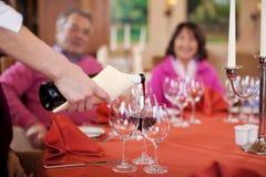 Camarera que vierte el vino rojo en los vidrios de la huésped Fotos de archivo