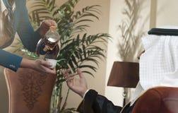 Camarera Serving Arabic Coffee a un hombre árabe rico foto de archivo libre de regalías