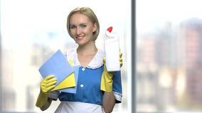 Camarera sonriente bonita que lleva a cabo fuentes de limpieza almacen de metraje de vídeo
