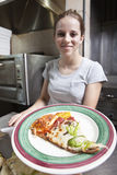 Camarera sonriente cómoda que sirve una rebanada de pizza Imagenes de archivo